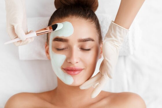 Beautician applying clay face mask on woman face
